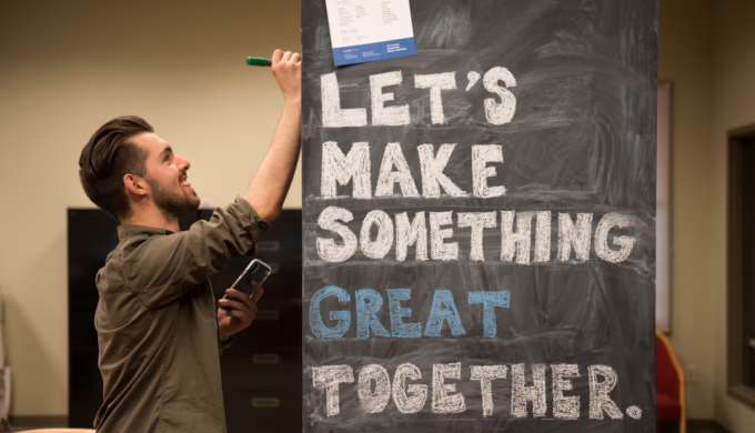 "Smiling student writing on chalkboard that says ""Let's Make Something Great Together."""